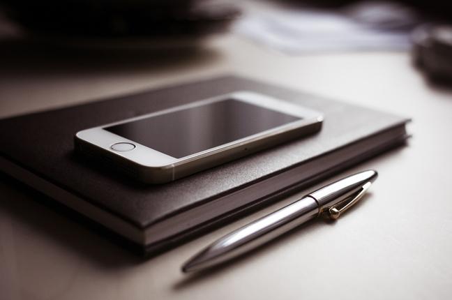 Un'agenda e uno smartphone, utili strumenti su cui appuntare i recapiti di Ottica Galuzzi: telefono e fax