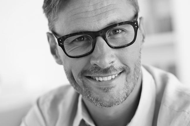 """Un uomo indossa occhiali da vista con lenti Zeiss; queste si riconoscono dal certificato di autenticità e da una piccola """"Z"""" incisa"""