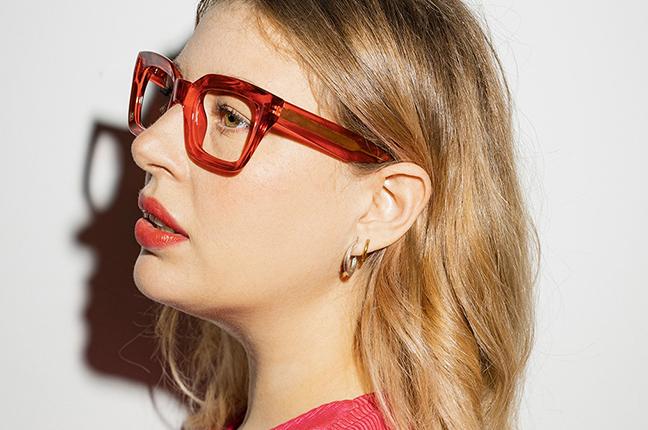 """Una ragazza indossa il modello """"PATACA"""" degli occhiali da vista Saraghina, nella versione """"ROSSO RUBINO CRISTALLO LUCIDO"""""""